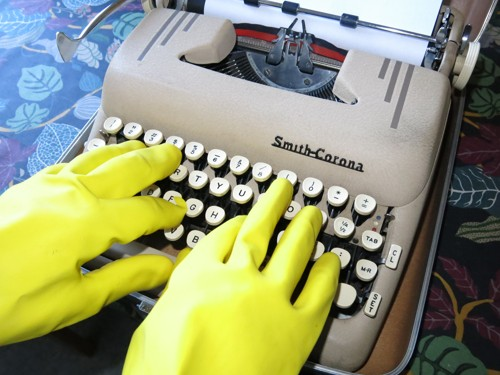 Using rubber gloves while typing on an old Smith-Corona typewriter.